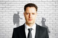Man with angel and demon shadows stock images