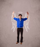 Man with angel illustrated wings on grungy background. Young man with angel illustrated wings on grungy background Stock Photo