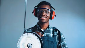Man with angle grinder machine. Young African-American man construction worker with angle grinder machine wearing safety ear muffs and checked shirt with stock video