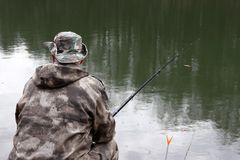 Fisherman in camouflage clothes sitting with a fishing rod on the shore. Man angling on the lake in spring, trees are reflected in the water stock photos