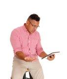 Man angry at his tablet computer. Royalty Free Stock Image