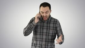 Man angry talking on telephone and walking on gradient background. stock photo