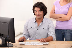Man and an angry womanm. Man repainring computer and an angry woman Royalty Free Stock Images
