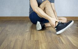 Man ankle pain from running, jogging, walking, sit on the floor.  stock image
