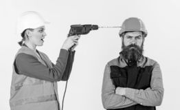 Man with annoyed face in helmet. Family making repair,. Husband annoyed by wife. Builder makes hole in male head. Annoying repair concept. Woman with happy face royalty free stock photography