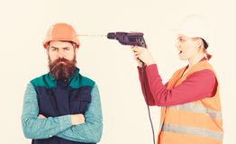 Man with annoyed face in helmet. Family making repair,. Husband annoyed by wife. Builder makes hole in male head. Annoying repair concept. Woman with happy face stock image
