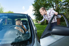 Man annoyed with female driver. Young men mad at female driver holding door Royalty Free Stock Photography