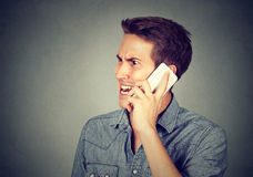 Man annoyed, frustrated pissed by someone talking on mobile phone. Closeup portrait man frustrated, pissed off by someone talking on mobile phone isolated on Stock Photos
