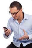 Man annoyed by his mobile phone. Studio shot over white of a young man who is exasperated by the text message he has just received royalty free stock image