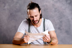 Man is annoyed about a letter. Young man is annoyed about a letter Royalty Free Stock Photo