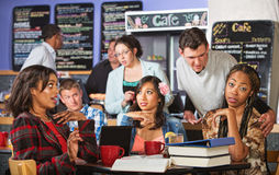 Man Annoying Students in Cafe Stock Images