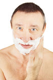 Man is anointing shaving foam on his cheeks. Over white background Royalty Free Stock Photography