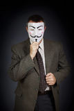 Man with anonymous mask against dark background Royalty Free Stock Photo