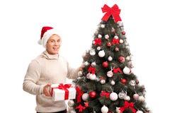 Man anseendet av en julgran och ett innehav en gåva Fotografering för Bildbyråer