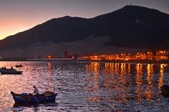 Man anseendet i fartygrodd på den sena aftonen med kust- ljus och berg i bakgrund Royaltyfri Foto