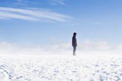 Man anseendet i snökastby mot blå himmel Arkivbilder