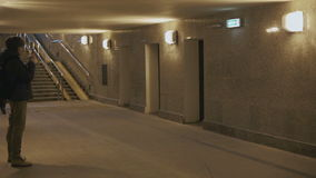 Man anseendet med en smartphone i gångtunnelen arkivfilmer