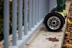 Man anseendet nära staketet på den svarta hoverboarden Fotografering för Bildbyråer