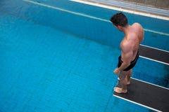 Man anseendet på dykningbräde på den offentliga simbassängen Arkivfoton