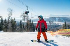 Man anseendet på hans snowboard med synligt behind för skidliftar Royaltyfri Foto