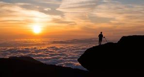 Man anseendet på klippan ovanför den molniga dalen Royaltyfria Bilder
