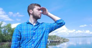 Man anseendet på kusten av havet på blåsväder som ler och ser in i avståndet Blick för ung man in i stock video