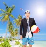 Man anseendet på stranden med snorkel- och strandbollen Royaltyfria Bilder