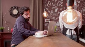 Man answers a phone call while working on his computer and drinking coffee. Multitasking young businessman stock video footage