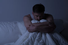 Man with anxiety disorder. Miserable man with anxiety disorder sitting in bed frightened stock photos
