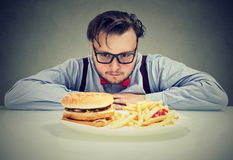 Man anxious about unhealthy fast food royalty free stock image