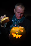 Man anxiously peering into glowing pumpkin Stock Photography