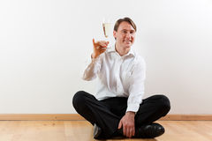 Man in apartment with champagne Royalty Free Stock Photos