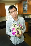 Man apologizing. Man holding bouquet of flowers looking sorry and asking forgiveness royalty free stock images