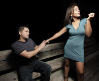 Man apologizing. Woman upset at the man and the man is holding the woman's hand and apologizing Stock Photo