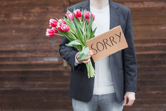 Man apologizing. Man holding a bunch of tulips and a card reading sorry Stock Image