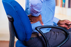 Man apparently working, sitting in a chair and holding his back, pain signal Stock Images