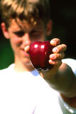 Man With Apple. Man holding apple out with face out of focus and apple in focus royalty free stock photography