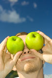 Man with apple. S on eyes Royalty Free Stock Image
