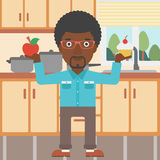 Man with apple and cake. An african-american man standing in the kitchen with apple and cake in hands symbolizing choice between healthy and unhealthy food Royalty Free Stock Photo