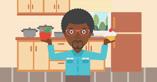 Man with apple and cake. An african-american man standing in the kitchen with apple and cake in hands symbolizing choice between healthy and unhealthy food Royalty Free Stock Photos