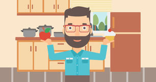 Man with apple and cake. A hipster man with the beard standing in the kitchen with apple and cake in hands symbolizing choice between healthy and unhealthy food Royalty Free Stock Photography