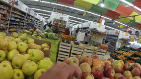 Man apple chooses pear bought in the store the stock footage