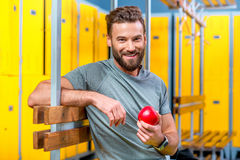 Man with apple in the gym stock photos