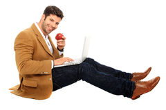 Man with apple and laptop. Sitting man working on computer while holds an apple in his hand Royalty Free Stock Images