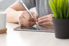 Man with Apple Pencil drawing on the iPad Pro Stock Photo