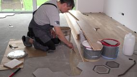 Man apply glue adhesive on floor for parquet board laying. Static shot stock video footage
