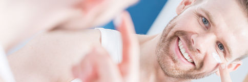 Man applying anti-aging cream. Metrosexual handsome man applying anti-aging cream Stock Image