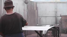 Man applying anti-corrosion powder coating metal sheet with spray gun in factory. Old man worker applying anti-corrosion powder coating to metal sheet in slow stock video footage