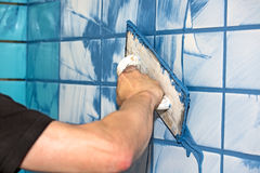 Man applying blue grout to white tiles. Workman or builder applying blue grout to white interior tiles in a house in a concept of DIY or decorating, close up Stock Image