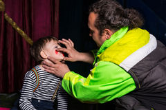 Man Applying Clown Make Up to Boys Face Royalty Free Stock Photo